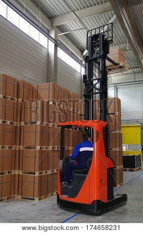 Warehouse worker driving forklift with palette.  Forklift moving pallets in warehouse.