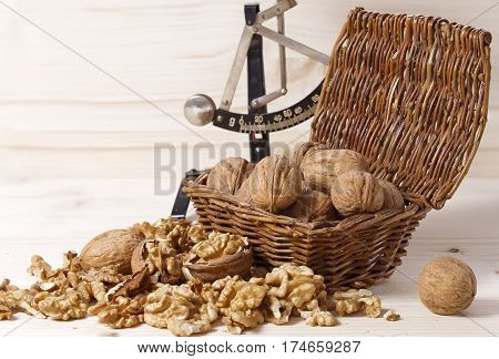 Many walnuts shelled and in-shell macro in a wicker basket with kitchen scales