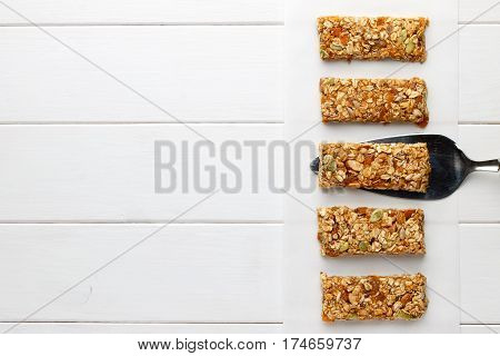 Homemade no bake granola bars on white wooden background. Top view copy space.