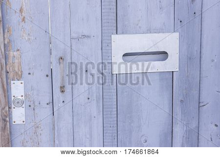 Old shabby wooden door with a lock and a post window on the street close up