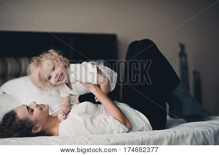 Happy young mother playing with her little baby girl in bed in hotel room. Family time. Motherhood.