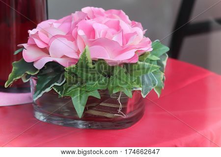 light pink cloth floral with green cloth leaves on red table