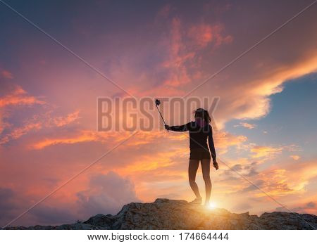 Beautiful young woman makes selfie for Instagram at sunset. Landscape with girl is photographing herself on the mountain peak against colorful sky with orange and red clouds. Lifestyle background