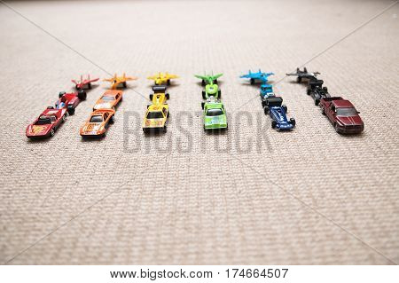 Toy cars collection on carpet.Sorted by color. Transportation airplane plane and helicopter toys for children miniature models. Many cars for little boys.