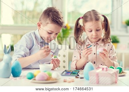 Two Happy Children Having Fun During Painting Eggs For Easter In Spring