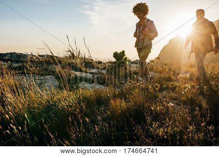 Friends on walk through countryside together. Young man and woman hiking on a summer day.
