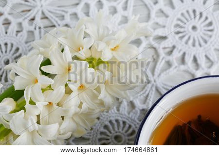 Cup of green tea color macaroon and white hyacinth flowers on a white lace tablecloth