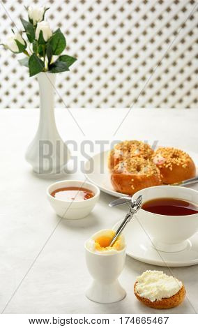 Delicious and healthy breakfast of boiled egg and brioche buns with black tea on a light background. Soft focus.