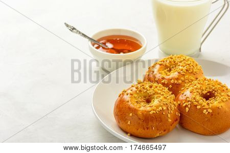 Delicious and healthy breakfast of brioche buns with milk and honey on a light background. Copy space soft focus.