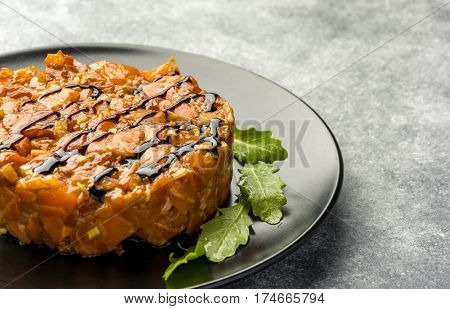 Delicious the tar-tare sauce from a salmon rich in omega 3 oil with aromatic herbs and spices with a lemon on black background. Healthy and diet food.