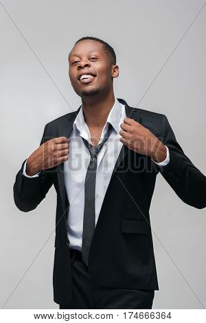 Happy african american guy in suit on grey background. Good luck, getting new job, success in business.
