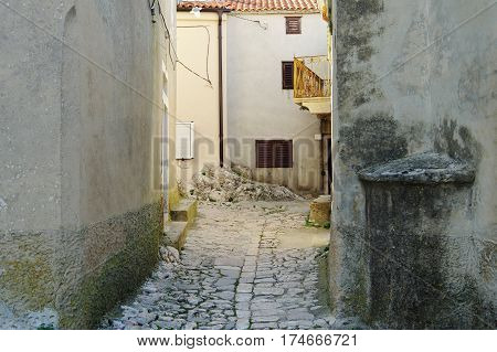 Vrbnik Croatia. A small town located on the Krk Island. The oldest parts of the old town was built in the fourteenth century. The narrow street of the old city with buildings typical of the region.
