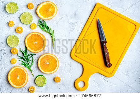 fruit design with cut blood orange, lime and knife on gray stone table background top view