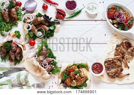 Tasty grilled meals frame on wood flat lay. Top view on assortment of hot bbq meat snacks, free space on white wooden table. Buffet, lunch, restaurant menu concept