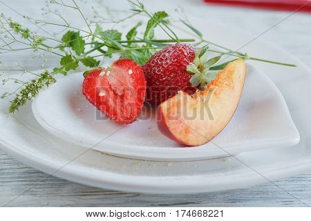 Strawberry and peach with mint on a white heard shape plate