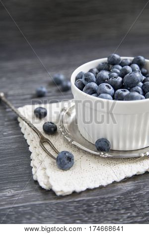 Cup with blueberry on a wooden background