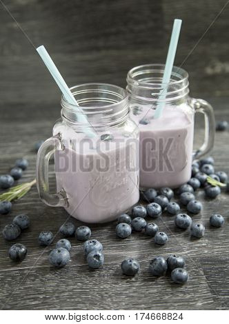 Jar with blueberry and smoothies on a wooden background