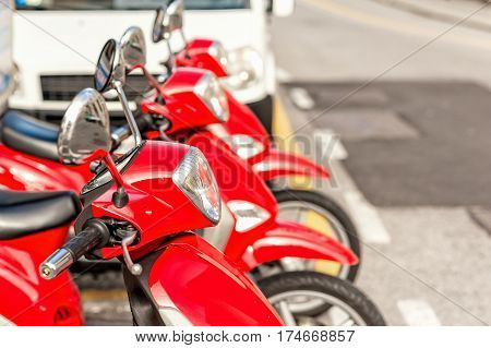 Motor scooters parked in rows. Red scooter. Selective focus. Scooters for home delivery of pizza.