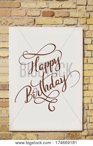 brick wall and white sheet and text Happy Birthday. Calligraphy lettering.