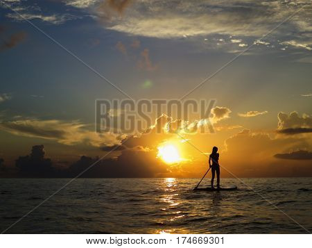 Woman in the Caribbean sea paddleboarding, Playa del Carmen, Mexico