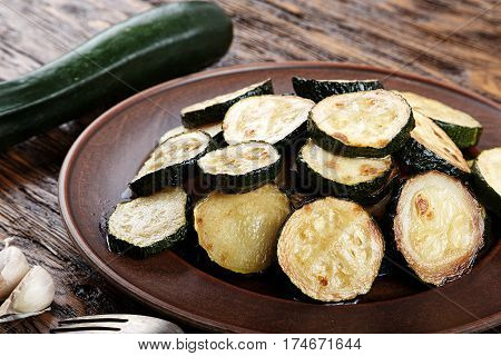 Fried zucchini in a clay plate on a wooden table. burlap on the table two raw zucchini and garlic. Horizontal photo with free space area for text or design.