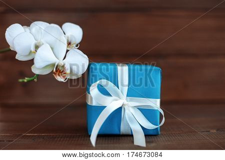 Gift and orchid on wooden background. The concept of celebration and a welcome card.