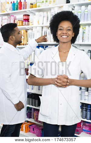 Pharmacist With Hands Clasped Smiling While Colleague Arranging