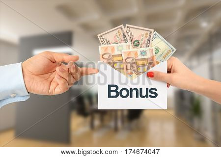 Bonus payment for salary or sales concept with businesswoman handing  to a businessman an envelope full of money