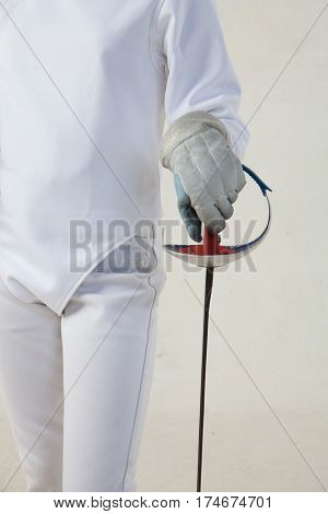 Female fencer hold the epee and wearing white fencing costume isolated on white background
