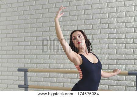 Ballerina stretches herself near barre in the classroom, beautiful women weared in black bodysuit practicing ballet.