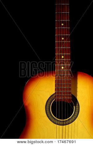 Acoustic guitar in yellow light. Isolated on black