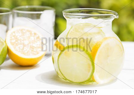 Detox drink with lemon on white wooden background