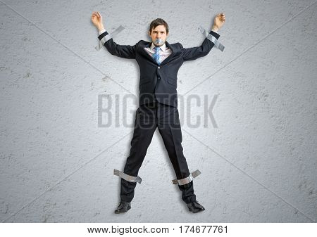 Businessman In Suit Is Taped To The Wall With Adhesive Tape.