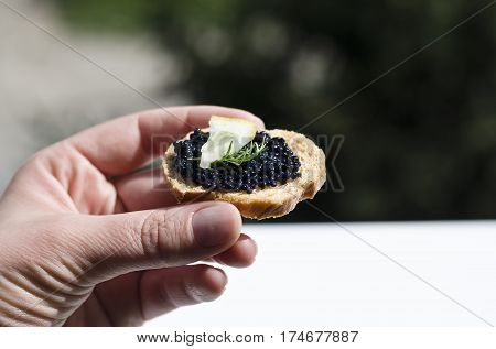 A woman hand with caviar, bruschetta and lemon