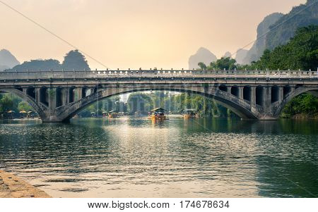 Yangshuo, China - September 23, 2016: Boats With Tourists Floating On Li River, Below A Stone Bridge