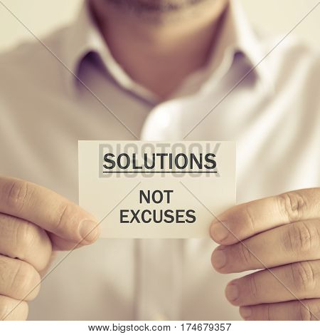 Businessman Holding Solutions Not Excuses Message Card