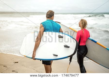 Athletic couple of surfers walks with surfboards on the beach on the background of the ocean waves and the sky. Girl wears a black-pink swimsuit. Guy wears a cyan T-shirt and black shorts.