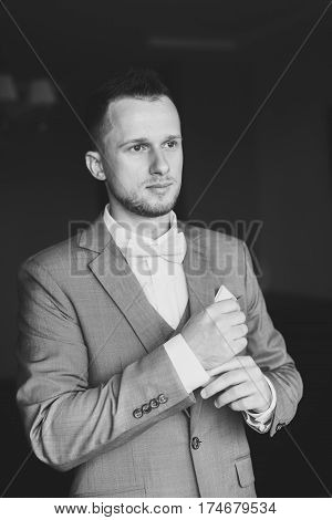 Elegant young fashion man dressing up for wedding celebration. Handsome groom dressed in gray suit white shirt and pink bow tie getting ready for event. Groom buttoning shirt. Black and white photo.