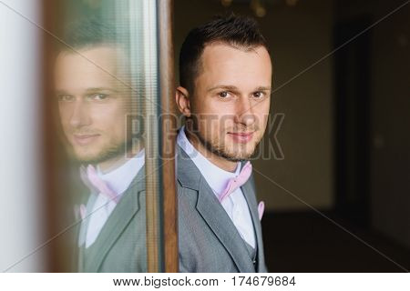 Elegant young fashion man dressing up for wedding celebration. Portrait of young man wearing bow tie and suit. Groom silhouette reflected in the window.