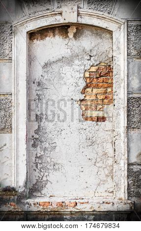 Old vintage cracked and damaged niche or blind window on historical architecture building facade made of brick and white concrete as background