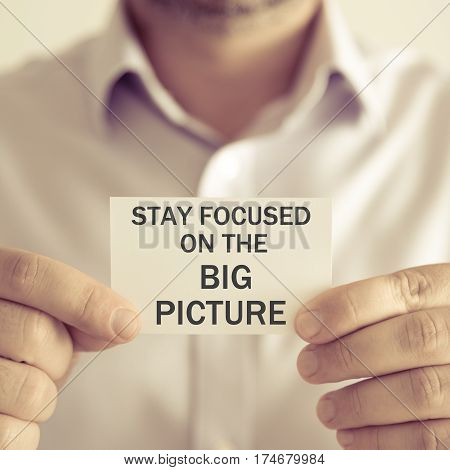 Businessman Holding Stay Focused On The Big Picture Message Card