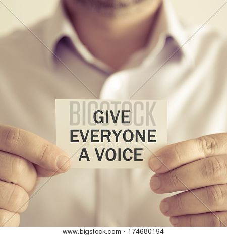 Businessman Holding Give Everyone A Voice Message Card