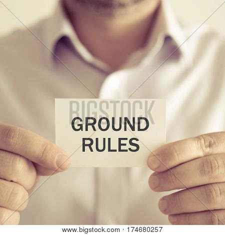 Businessman Holding Ground Rules Message Card