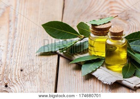 Healthy lifestyle concept. Natural bay laurel essential oil, essence in glass bottle with leaves on a rustic wooden table for beauty, spa, therapy. Copy space background