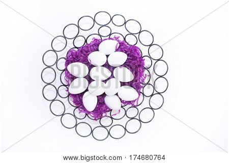 Black basket made with metal circles with purple paper grass and a dozen white hen's eggs from above against a white background.