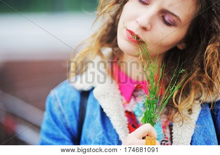 Young pretty girl with closed eyes on the street in the city blurred background closeup.
