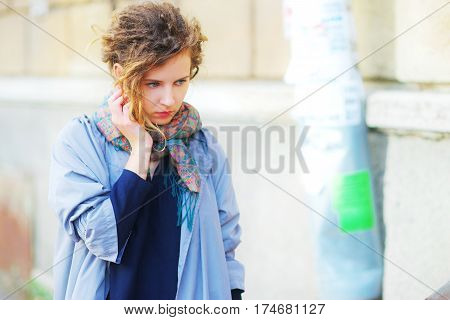 Portrait of a young the pensive girl about a stone wall closeup.