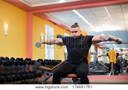 Handsome powerful athletic man doing barbell shoulder press exercise. Strong bodybuilder with perfect muscles