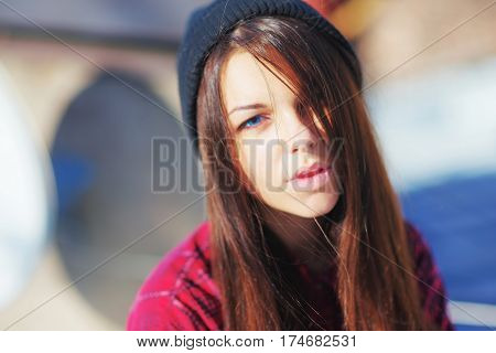 Portrait of a young successful beautiful long-haired girl brunettes with blue eyes on the street closeup