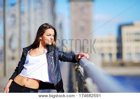 Portrait of young cute girl brunette in a short white t-shirt and black jacket leaning on the railing of promenade on a Sunny day.
